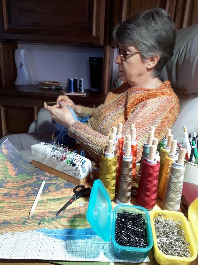 Gabriele Tippel gemütlich im Sessel sitzend und an einem Wandbild, einer gestrickten Landschaft in KlugeStrickArt arbeitend