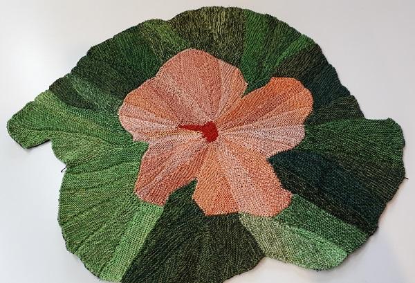 Gabriele Tippel - Hier sieht man meine gestrickte rosa Hibiskusblüte mit grünem Hintergrund in KlugeStrickArt als Tischdeko
